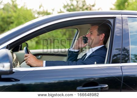 Businessman talking on cell phone while driving, not paying attention to the road and traffic.