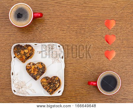 Two red cups of coffee white square dish with three heart-shaped cakes in the lower left corner and red hearts at the right edge. View from above