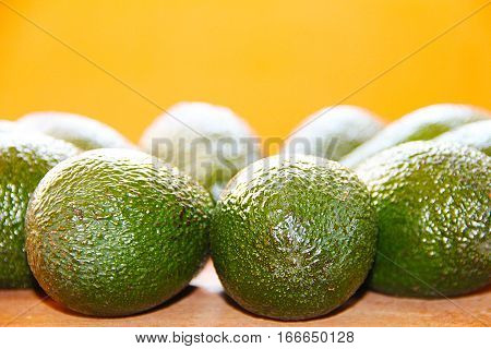 The green avocado on a wooden board on an orange background.