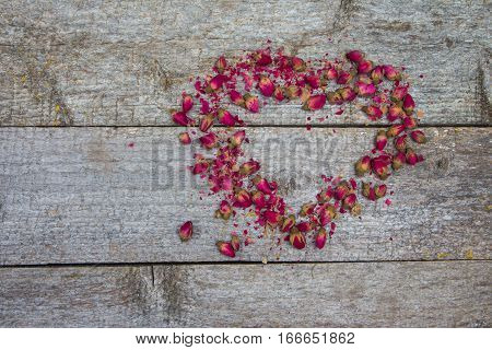 Rosebuds On Rustic Wooden Table In Shape Of Heart