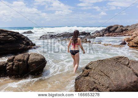 Girl teenager entering beach ocean waves rock tidal pool summer holidays.
