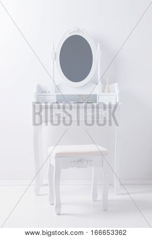 portrait of vintage vanity table mirror set with stool and accessories on white wall
