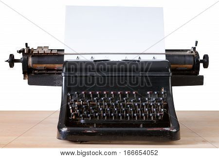 Vintage typewriter with paper sheet on wooden table isolated on white. Old writing equipment. Press, blogging and journalism concept background