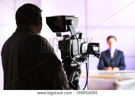 Closeup of a Camera Operator Filming an Anchorman