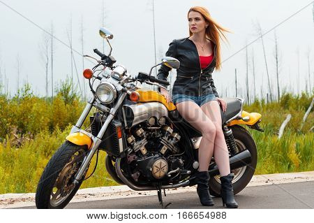 beautiful sexy woman with motorcycle on the road