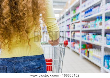 Closeup of a Woman Pushing a Shopping Cart in a Supermarket