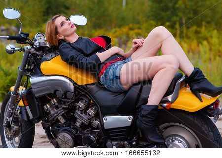 sexy young biker woman lying on motorcycle