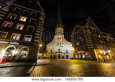 RIGA LATVIA - 1ST JAN 2017: St. Peter's Church and other buildings in Riga's Old Town at night.