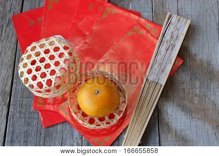 Top view of orange in a basket on old wooden board with Chinese red envelope packet or ang pao and hand blow background. Happy Chinese new year concept.
