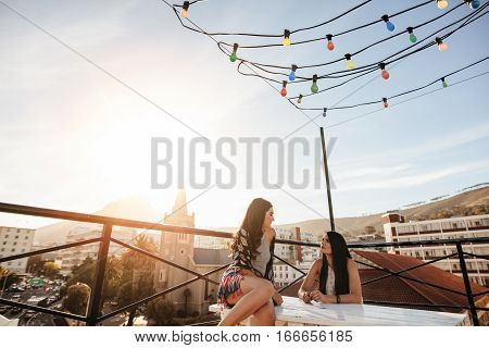 Two female friends during rooftop party. Young women sitting on rooftop and talking.