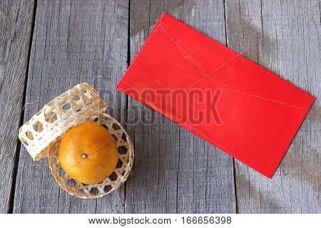 Top view of orange in a basket on old wooden board with Chinese red envelope packet or ang pao background. Happy Chinese new year concept.