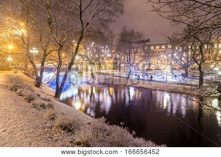 RIGA LATVIA - 2ND JAN 2017: A view of Bastejkalna park in Riga in the winter at night. Snow an d people can be seen.