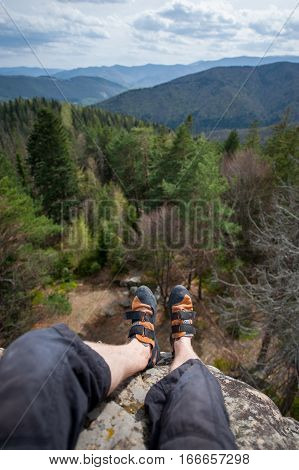Focus an astonishing view mountain and forest valley at day with legs and feet in first freedom concept. Climbing shoes. Wide angle lens