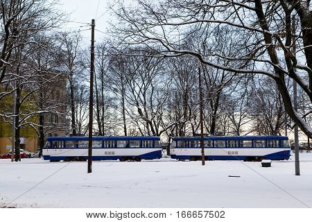 RIGA LATVIA - 3RD JAN 2017: Trams in Riga during the day in the winter. Lots of snow can be seen.