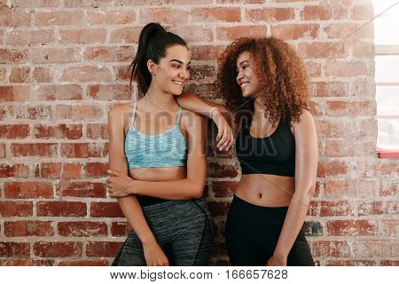 Portrait of two fitness females in gym relaxing and talking after workout. Young woman friends standing against wall and smiling.