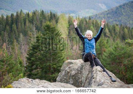 Female Climber On The Peak Of Rock