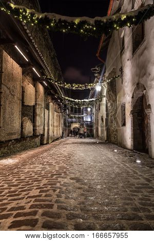 TALLINN ESTONIA - 3RD JAN 2017: A view along St. Catherine's Passage in Tallinn at night. Tomb Stones can be seen on the left hand side. People can be seen in the distance.
