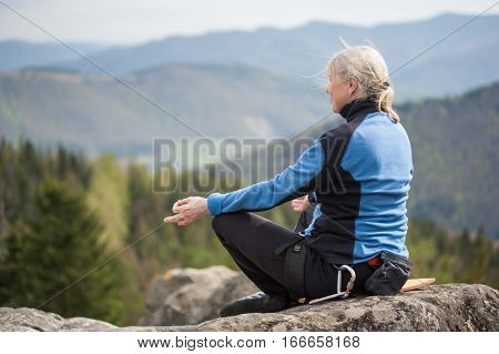 Female Climber On The Peak Of Rock With Climbing Equipment