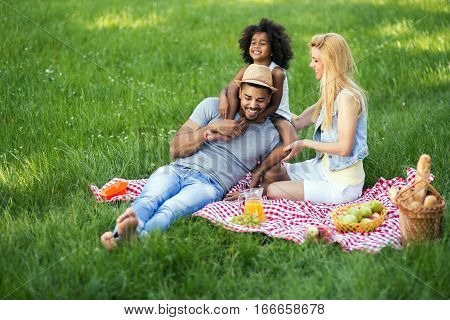 Happy cute family enjoying picnic in nature