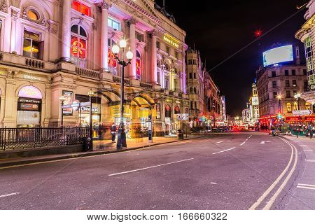 LONDON UK - 8TH MARCH 2015: Coventry Street near Picadilly Circus at night. The blur of people can be seen.