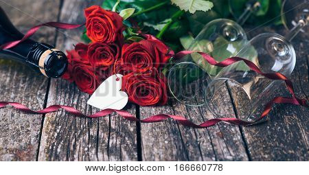 Valentines day cards. Bouquet of red roses two glasses bottle of wine gift box with tag on vintage wooden board. Vintage toned.