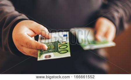 Man giving money cash. Male hands holding hundred euro banknote bill. Credit or lend concept.