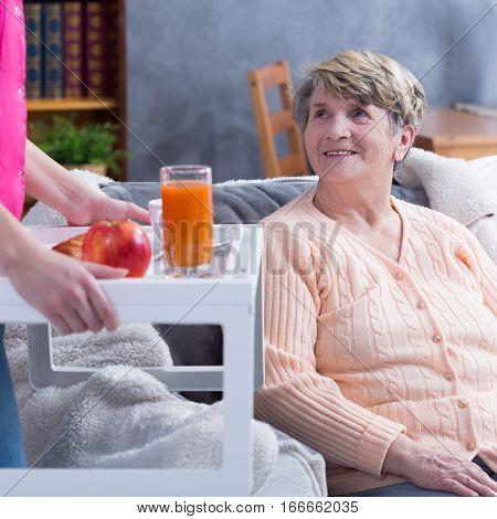 Caregiver Serving Senior Woman Juice