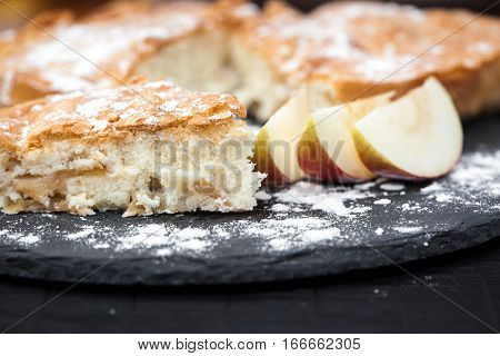 homemade appetizing Apple pie with powdered sugar and Apple slices