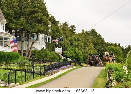 MACKINAC ISLAND, MI - JULY, 2016: A horse drawn carriage drives tourist along the west bluff cottage area.