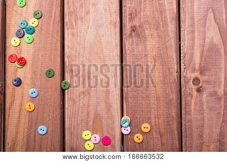 buttons scattered on a brown wooden table