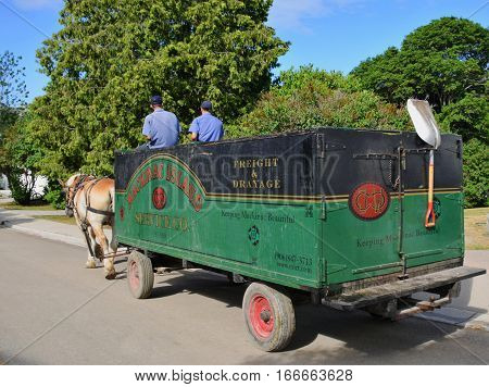 MACKINAC ISLAND - JULY, 2016: With no motorized vehicles allowed on the island, the garbage man also does his job with a horse drawn wagon.