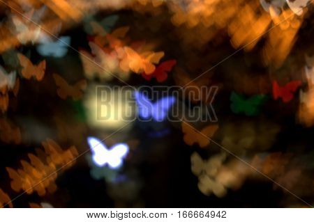 abstract butterflies of numerous multi color on a dark golden background bokeh effect