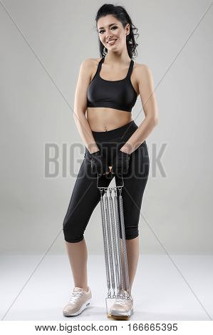 Fitness woman in sportswear doing exercises with expander