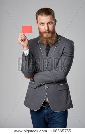 Hipster business man with beard and mustashes in suit standing over grey background holding credit card