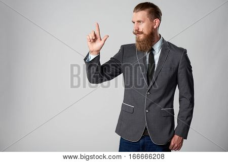 Confident stylish business man pointing to side, pressing imaginary button at blank copy space over grey background