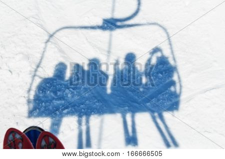 Shadow of skiers on a ski lift at winter mountain resort