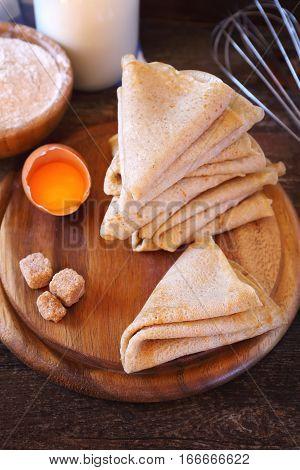 Pancakes and ingredients: flour milk sugar on wooden background