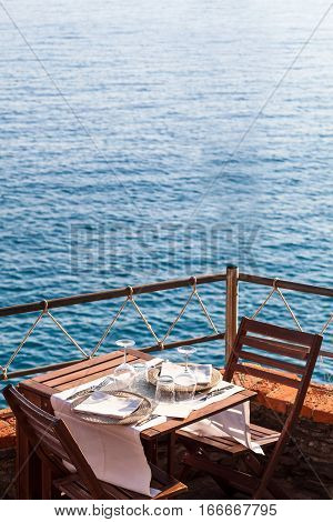 Wooden table with white dishwater and chairs on ocean in a restaurant in Italy Europe
