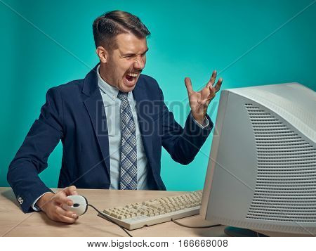 Angry fury businessman using a monitor against a blue studio background