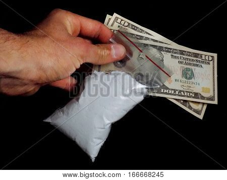 Drug dealer holding bag with cocaine drug powder and dollar bills money, men selling drugs junkie on black background in black and white colors