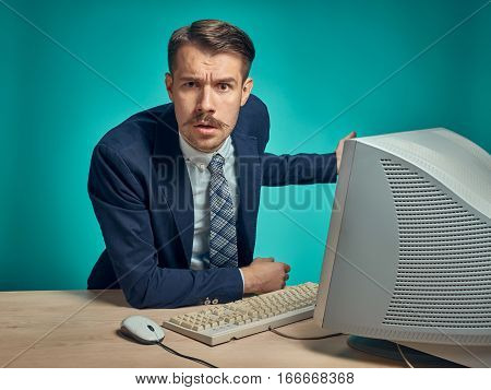 The sad, puzzled, disappointed young man in a business suit working on computer at desk on blue studio background