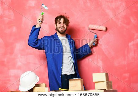Smiling Man Holding Paint Rollers