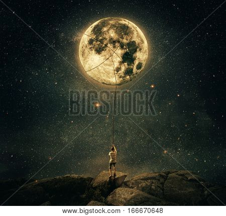 Imaginary view as a young man holding a rope try to catch and pull the full moon from the night sky. Achievement and hard determination concept.