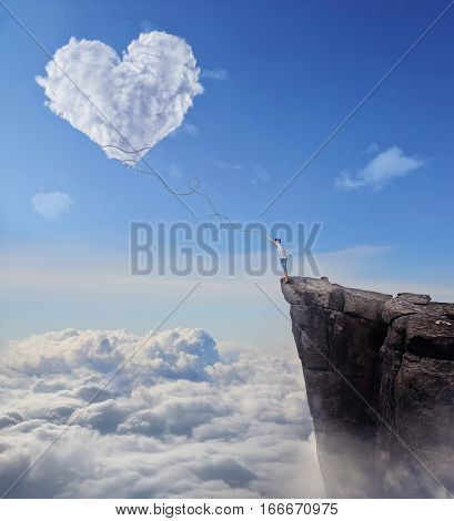 Imaginary view with a boy on the edge of a cliff trying to catch a heart shaped cloud with a long rope. Follow your heart concept.