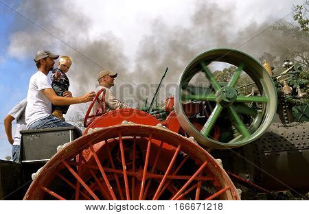 ROLLAG, MINNESOTA, Sept 2, 2016: Two unidentified men and a child operate an old restored steam engine in a parade at the West Central Steam Threshers Reunion in Rollag, MN attended by 1000's held annually on Labor Day weekend.