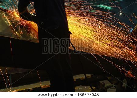 Welder used grinding stone on steel in manufacturing with sparks