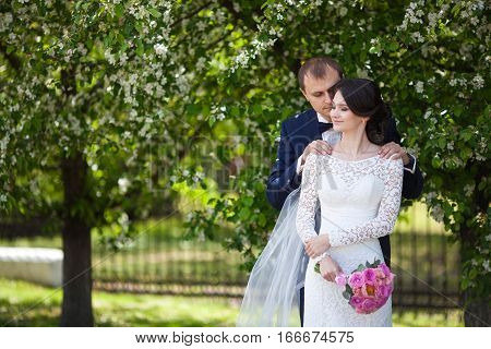 Young newlywed groom and bride with pink wedding bouquet in blooming garden