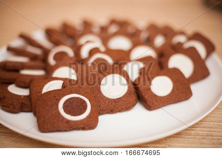 Chocolate cookies in photocamera shape on white plate shallow dof