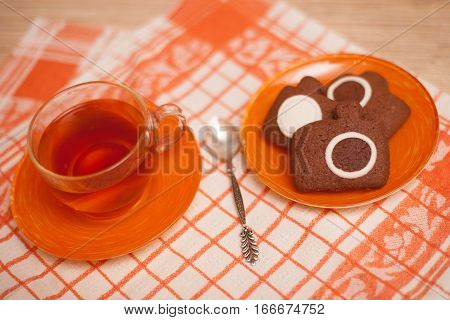 Chocolate cookies in photocamera shape and cup of tea shallow dof