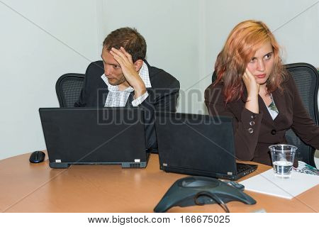 Young unhappy business woman and man at conference table with laptops turning away from each other